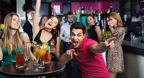 Portrait of smiling females and males having fun. Portrait of positive females and males having fun in the bar Stock Photo