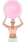 Portrait of a smiling fit woman holding up fitness ball Stock Photo