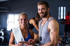 Portrait of smiling fitness instructor with woman in gym. Portrait of smiling fitness instructor with woman standing in gym Stock Photography