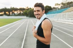 Portrait of a smiling fitness man with towel on shoulders. Young smiling man with towel on shoulders posing at camera on stadium after morning workout. Portrait Royalty Free Stock Images