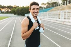 Portrait of a smiling fitness man with towel on shoulders. Young smiling man with towel on shoulders posing at camera on stadium after morning workout. Portrait Royalty Free Stock Photo