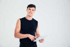 Portrait of a smiling fitness man using tablet computer Royalty Free Stock Image