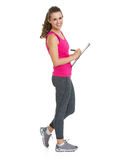 Portrait of smiling fitness trainer writing in clipboard Stock Image