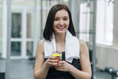 Portrait of smiling fitness woman with glass of water with lemon, woman in sportswear after fitness classes drinking water in gym.  stock photos