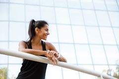 Portrait of a smiling fitness woman leaning on a rail Royalty Free Stock Image