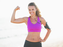 Portrait of smiling fitness young woman on beach showing biceps Stock Photo
