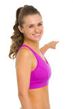 Smiling fitness woman pointing on copy space Royalty Free Stock Photos