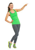 Portrait of smiling fitness young woman pointing on copy space Royalty Free Stock Image
