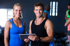 Portrait of smiling friends with digital tablet in gym Royalty Free Stock Photos