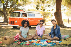 Portrait of smiling friends having food while sitting on picnic blanket Stock Photo