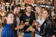 Portrait of smiling friends holding drinks while standing in bar Stock Photography