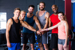 Portrait of smiling friends putting hands together in gym Stock Image