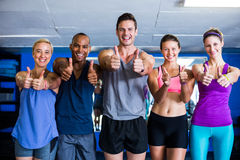 Portrait of smiling friends showing thumbs up in gym Royalty Free Stock Image
