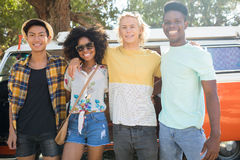 Portrait of smiling friends standing against camper van at campsite Royalty Free Stock Photography