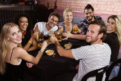Portrait of smiling friends toasting drinks while sitting together at nightclub Royalty Free Stock Photos