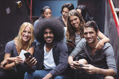 Portrait of smiling friends using mobile phones on steps at nightclub. Portrait of smiling young friends using mobile phones while sitting on steps at nightclub Royalty Free Stock Image
