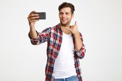 Portrait of a smiling funky man taking a selfie. While standing isolated over white background stock photos