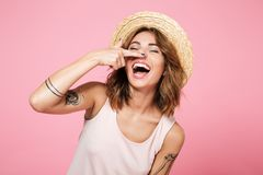 Portrait of a smiling funny girl in summer hat. Holding finger at her nose isolated over pink background Royalty Free Stock Image