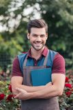 Smiling gardener in apron holding digital tablet in hands while standing in garden royalty free stock photography