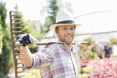 Portrait of smiling gardener carrying rake on shoulders at plant nursery Stock Photography