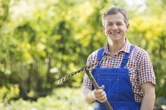 Portrait of smiling gardener holding rake in plant nursery Royalty Free Stock Image