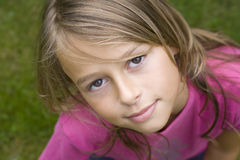 Portrait of smiling girl. Close up portrait of a ten year old girl, smiling up at the camera. Positive emotion Royalty Free Stock Image