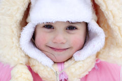 Portrait of the smiling girl. A portrait of the smiling girl wearing a bright pink coat and white fur hat Stock Images