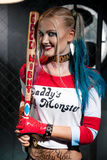 Portrait of smiling girl with a bat in costume Harley. Stock Photo
