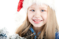 Portrait of a smiling girl with blue eyes in a Chr. Cute Portrait of a smiling girl with blue eyes in a Christmas hat with a Christmas tree Stock Photos
