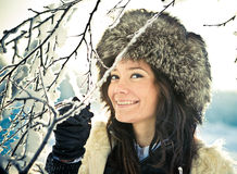 Portrait of a smiling girl with a branch in a fur. Cute portrait of a smiling girl with a branch in a fur hat Royalty Free Stock Images