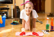 Portrait of smiling girl cleaning wooden floor with rag Stock Photography