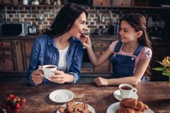 Girl feeding mother with cookie. Portrait of smiling girl feeding mother with cookie while drinking tea together in the kitchen Stock Images