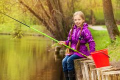 Portrait of smiling girl fishing near pond Royalty Free Stock Photos