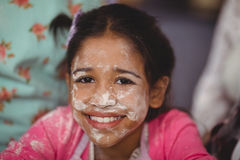 Portrait of smiling girl with flour on face Stock Photography