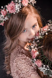 Portrait of smiling girl with flowers wreath on head. On black Royalty Free Stock Image
