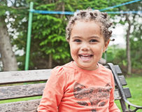Portrait of smiling girl in the garden. Portrait of happy smiling little girl sitting on a bench seat in the garden Stock Photos