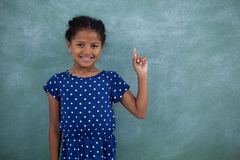 Portrait of smiling girl gesturing. While standing against wall Stock Photos