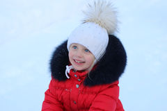 Portrait of a smiling girl in a hat with a big fur pompom winter. Joyful girl playing outdoors in winter Royalty Free Stock Photography