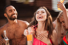 Portrait of a smiling girl having fun at pool party. Portrait of a smiling young girl in bikini having fun with friends at pool party outdoors Stock Photos