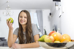 Portrait of smiling girl holding apple while sitting at table in house Royalty Free Stock Photo