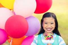 Portrait of smiling girl holding balloons and lollypop in the park Royalty Free Stock Image