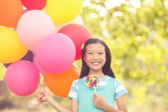 Portrait of smiling girl holding balloons and lollypop in the park Stock Photos