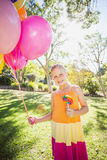 Portrait of smiling girl holding balloons and lollypop in the park Stock Photography