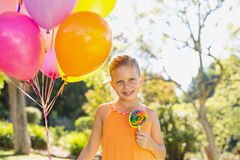 Portrait of smiling girl holding balloons and lollypop in the park Stock Image