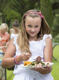 Portrait of smiling girl holding plate of barbecue Stock Photography