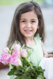 Portrait of smiling girl holding roses and gift box at home Stock Photo