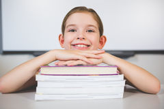 Portrait of smiling girl leaning on stack of books in class room Royalty Free Stock Photo