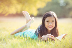 Portrait of smiling girl lying on grass and reading book in park Royalty Free Stock Image