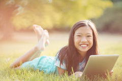 Portrait of smiling girl lying on grass and using digital tablet Royalty Free Stock Photography