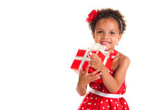 Portrait of a smiling girl mulatto with curly hair and a gift in hands. Birthday or New Year present.  Stock Photo